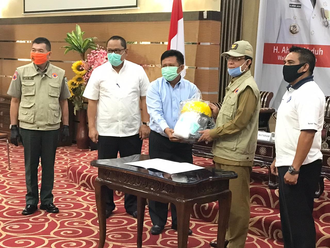 PEDULI: Direktur Utama PT Air Minum Giri Menang L. Ahmad Zaini (tiga dari kiri) memberikan bantuan APD secara simbolis kepada Wali Kota Mataram H. Ahyar Abduh di Aula Pendopo, kemarin.